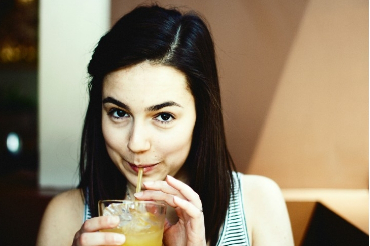 Woman is sipping from a glass of lemonade