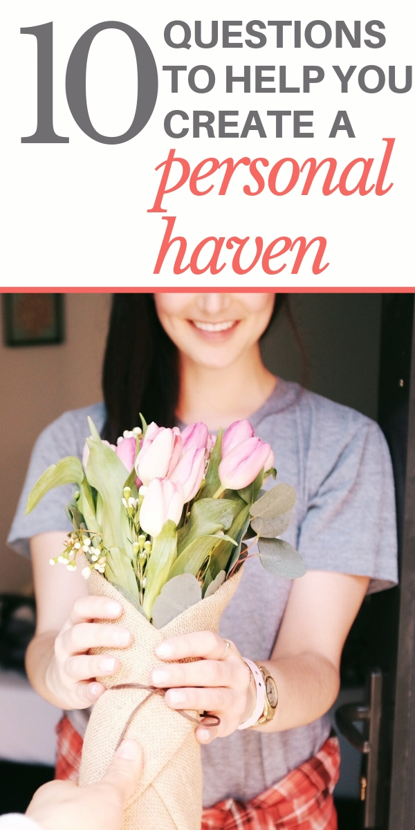 Woman is standing in the doorway of her haven, smiling and holding a bouquet of pink roses