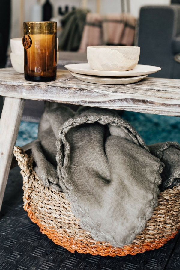 Basket filled with cozy blankets is tucked under a wooden bench