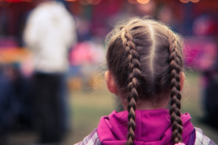 Girl with french braided pigtails stands looking at a fair