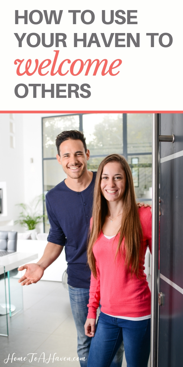 Smiling couple opens the front door of their home for guests