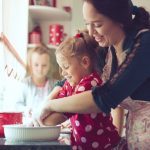 Mom helps daughters bake in the kitchen