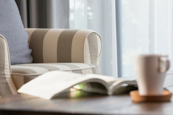 Cozy armchair with open book and mug of coffee