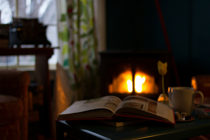 Cozy reading nook with a fireplace and book