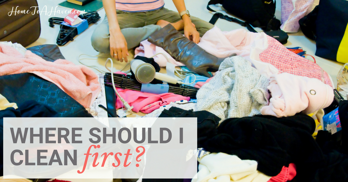 Woman sits in a messy pile of clothing and shoes