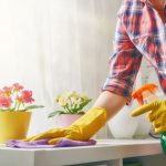 Woman cleaning a counter with a cloth and spray cleaner