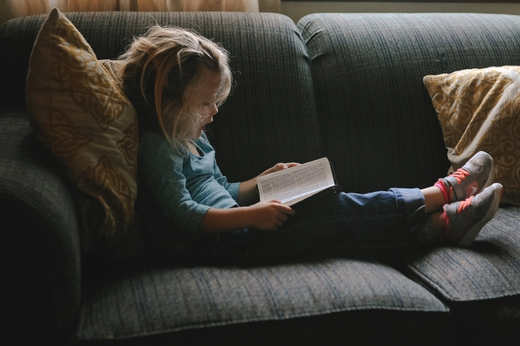 Little girl sits on a couch reading a book