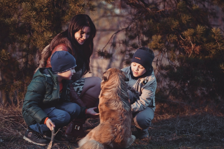 Mother and two young sons pet a dog outdoors