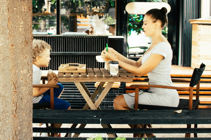 Mother and son sit at a picnic table eating lunch together