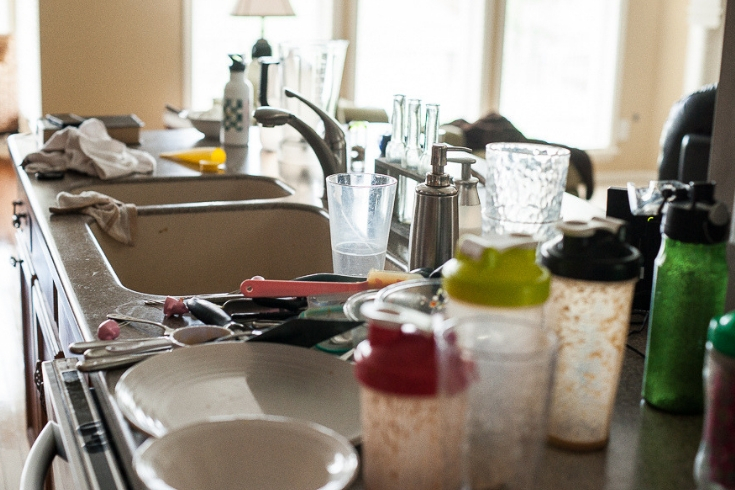 Messy kitchen counter piled with dirty dishes