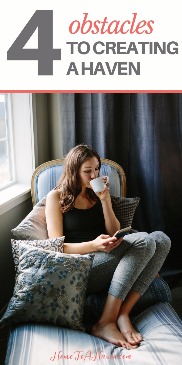 Woman is sitting cozily in a chair, sipping hot tea and scrolling her cell phone