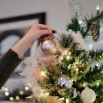 Woman decorates Christmas tree