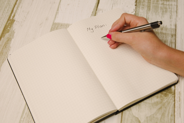 Woman writes plans in blank journal