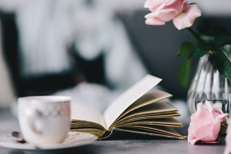 Open book is set in between a white tea cup and a vase