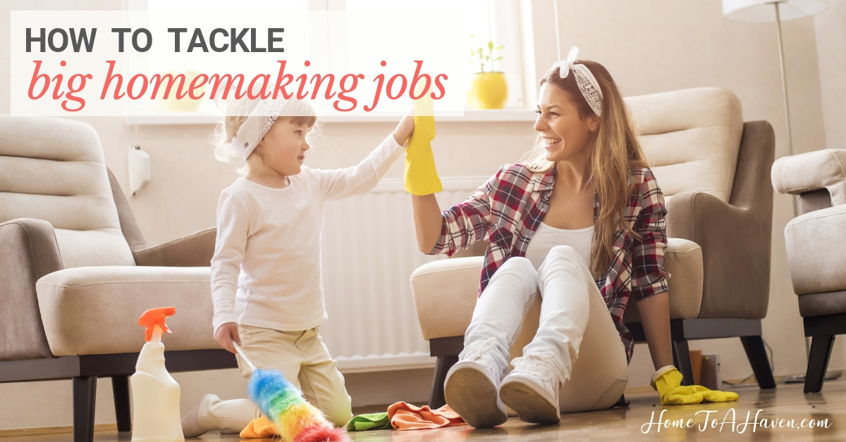 Mom and daughter sit on the floor with cleaning supplies
