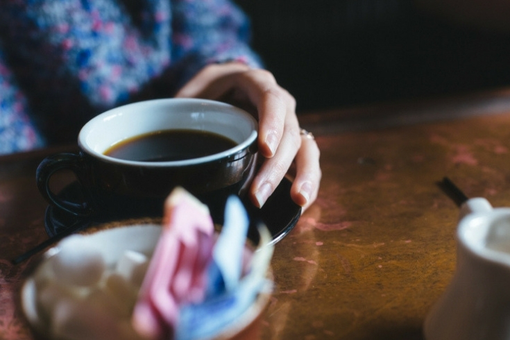 Woman carefully holds a mug of coffee