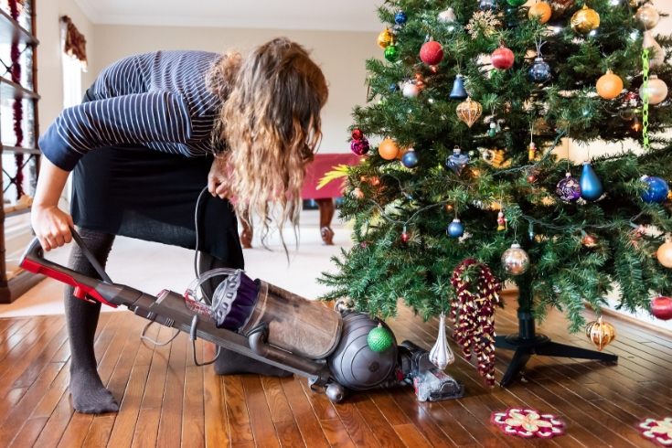 Woman vacuums under a Christmas tree