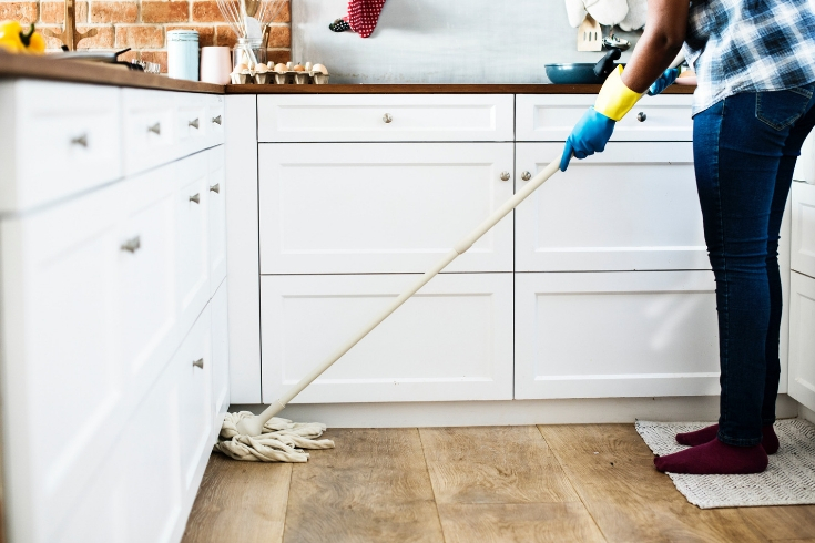 Woman mops kitchen floor