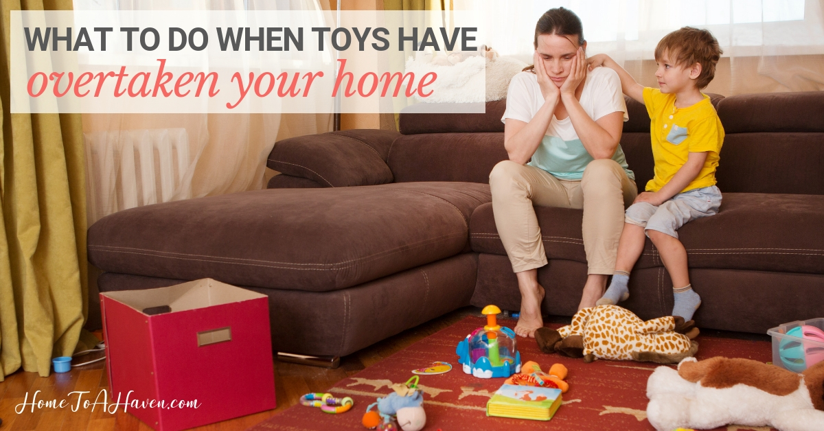 Mom sits on a couch with her head in her hands, frustrated by a mess of toys on the floor