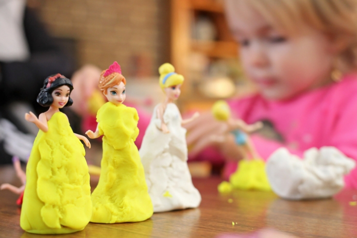 Little girl plays with Disney princesses and Play-Doh