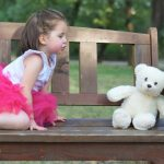 Little girl talks to a teddy bear while sitting on a bench
