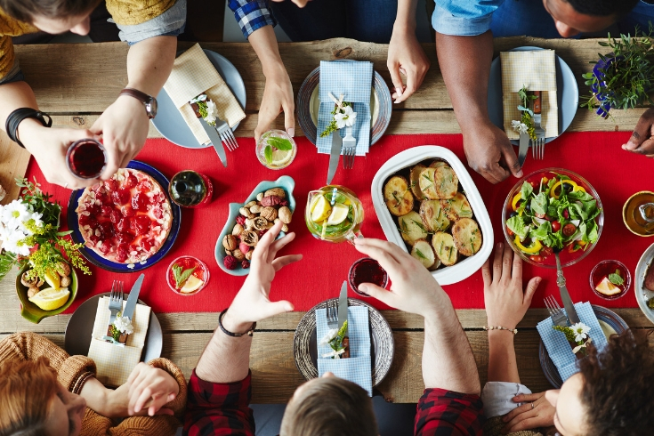 Group of friends gather around a Christmas dinner table