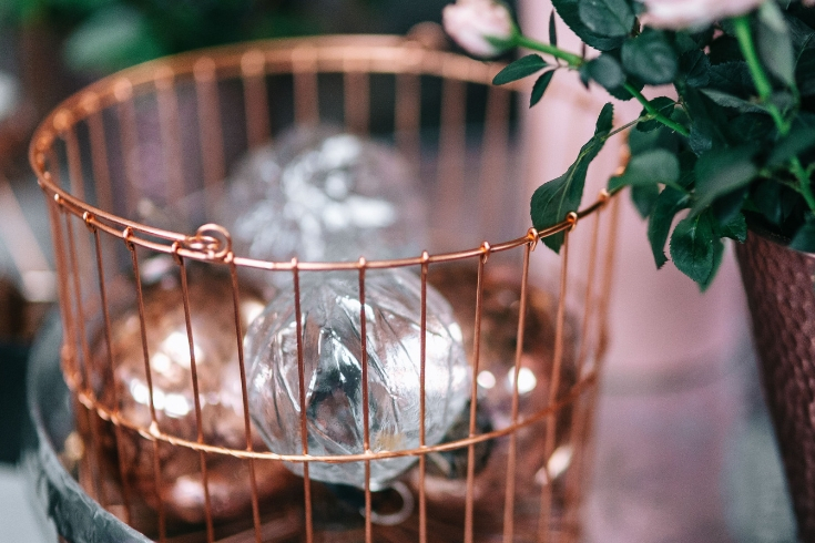 Wire basket filled with metallic and glass ornaments