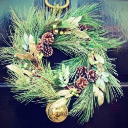 Pine wreath displayed on black front door