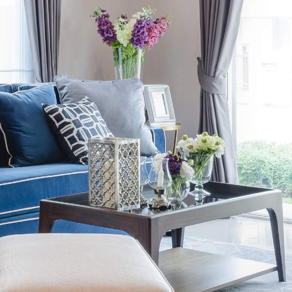 Comfortable living room is furnished with a blue couch, coffee table, lamp, and vase